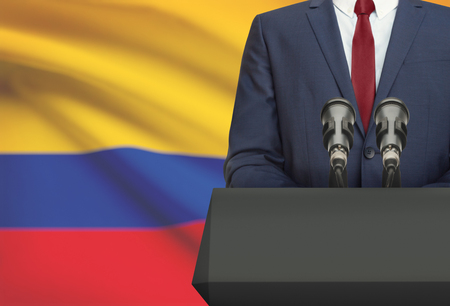 Businessman or politician making speech from behind the pulpit with national flag on background - Colombia