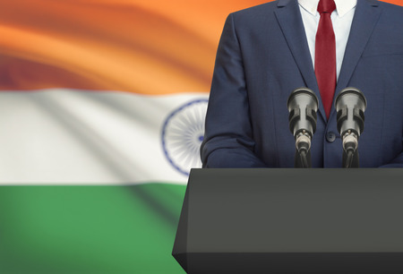 Businessman or politician making speech from behind the pulpit with national flag on background - India