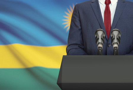 Businessman or politician making speech from behind the pulpit with national flag on background - Rwanda