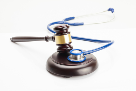 Close up studio shot of a judge gavel and a stethoscope