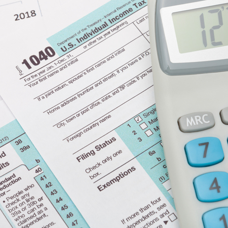 taxable income: USA 1040 Tax Form with calculator over it - close up shot