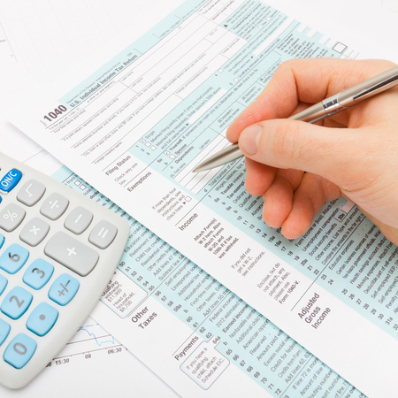 taxable income: Close up shot of a man filling out 1040 US Tax Form with calculator next to it - close up shot