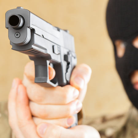Man in mask holding gun in front of him - close up shot