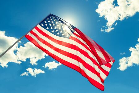 USA flag against sun - outdoors shoot. Filtered image: cross processed vintage effect. Stock Photo