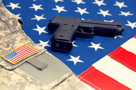 Handgun and US army uniform over huge US flag. Filtered image: cross processed vintage effect. Stock Photo