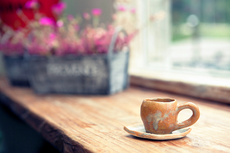Coffee cup in coffee shop with flowers on background. Filtered image: cross processed vintage effect. Stock Photo