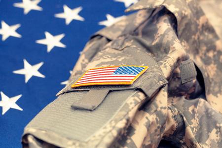 USA-Armeeuniform über US-Staatsflagge - Atelieraufnahme. Gefiltertes Bild: Kreuz verarbeiteter Weinleseeffekt.
