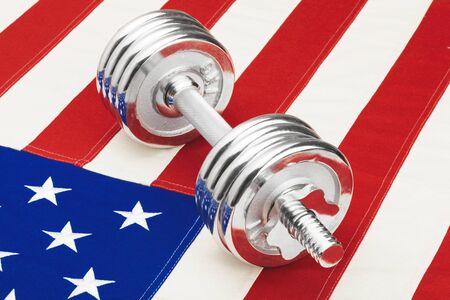 Metal dumbbells over US flag as symbol of healthy nation - close up studio shot. Filtered image: cross processed vintage effect.