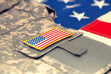 US flag with army uniform over it - studio shot. Filtered image: cross processed vintage effect.