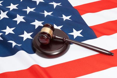 Studio shot of a judge gavel and soundboard laying over USA flag Stock Photo