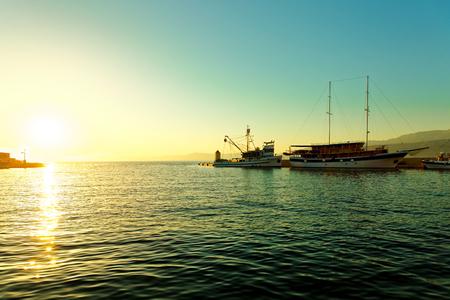 Sailboat and fishing trawler moored in the harbor of town Postira - Croatia, Brac island