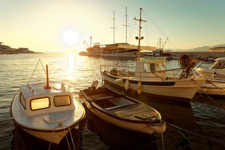Piccole barche e una barca a vela ormeggiata nel porto della città Postira - Croazia, isola di Brac