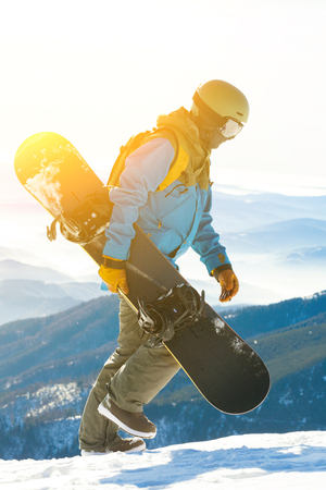 Young snowboarder walking at the very top of a mountain with sun behind him