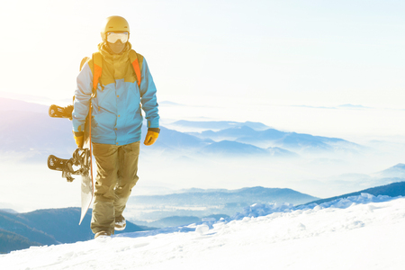 Snowboarder with sun behind him walking up the mountain holding snowboard in hand