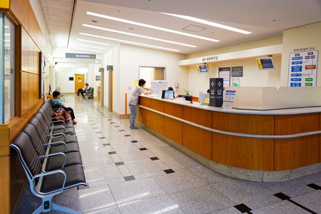 SEOUL, KOREA - AUGUST 12, 2015: One lady waiting at registration desk of Severance hospital of Yonsei University - prestigious high end hospital in Seoul, South Korea