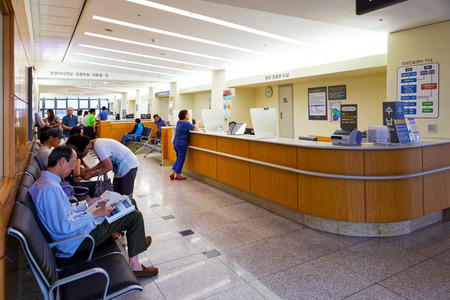 SEOUL, KOREA - AUGUST 12, 2015: People waiting at registration desk of Severance hospital of Yonsei University - prestigious high end hospital in Seoul, South Korea 免版税图像 - 86074485