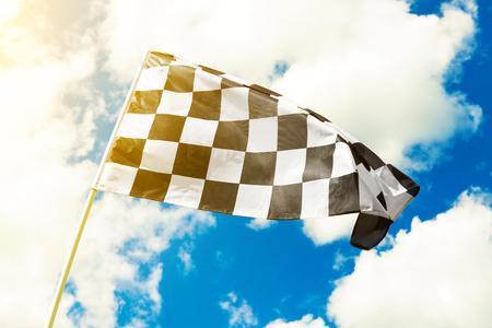 Geruite vlag die in de wind met zichtbare zonzon golven
