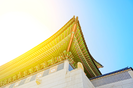 Roof top of the entrance to Gyeongbokgung Palace - translation for this word is Gyeongbokgung Palace - with sun flare captured - Seoul, South Korea