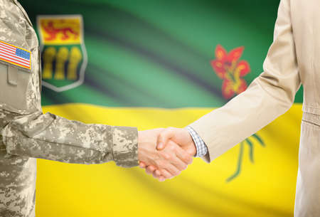 American soldier in uniform and civil man in suit shaking hands with certain  Canadian province flag on background - Saskatchewan