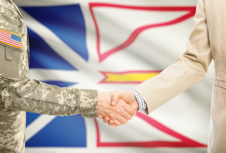 American soldier in uniform and civil man in suit shaking hands with certain  Canadian province flag on background - Newfoundland and Labrador
