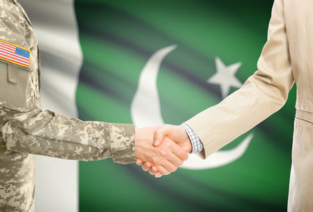 American soldier in uniform and civil man in suit shaking hands with adequate national flag on background - Pakistan