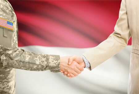 American soldier in uniform and civil man in suit shaking hands with adequate national flag on background - Indonesia