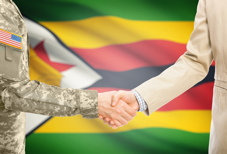 American soldier in uniform and civil man in suit shaking hands with adequate national flag on background - Zimbabwe