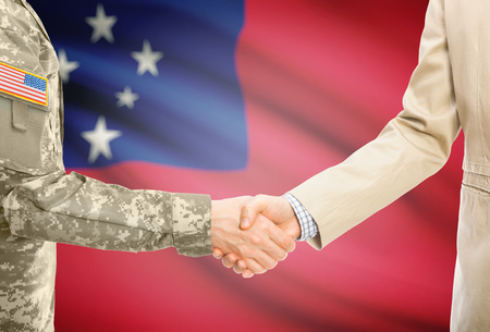 American soldier in uniform and civil man in suit shaking hands with adequate national flag on background - Samoa Stock Photo