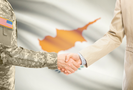 American soldier in uniform and civil man in suit shaking hands with adequate national flag on background - Cyprus