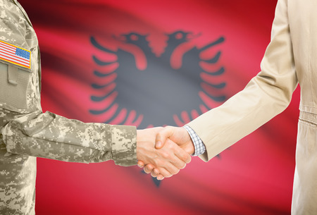 American soldier in uniform and civil man in suit shaking hands with adequate national flag on background - Albania