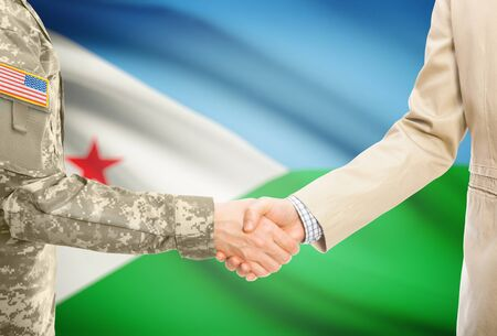 American soldier in uniform and civil man in suit shaking hands with adequate national flag on background - Djibouti Stock Photo