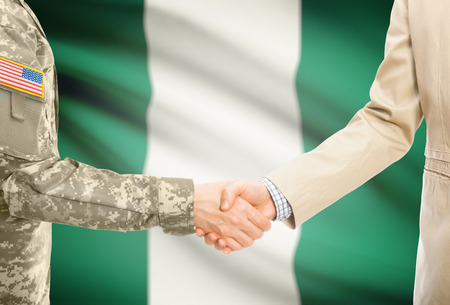 American soldier in uniform and civil man in suit shaking hands with adequate national flag on background - Nigeria Stock Photo