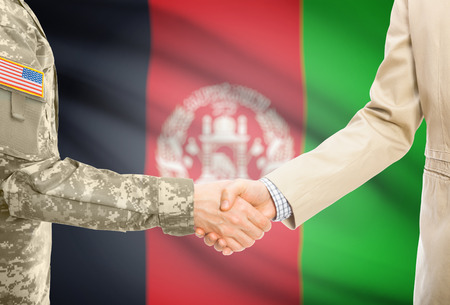 American soldier in uniform and civil man in suit shaking hands with adequate national flag on background - Afghanistan