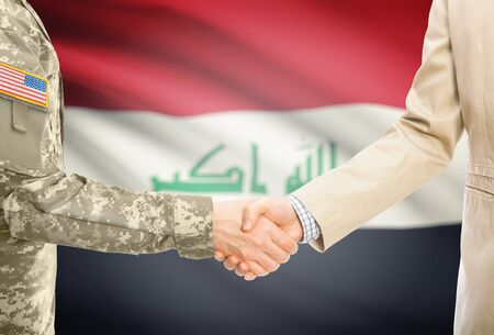 American soldier in uniform and civil man in suit shaking hands with adequate national flag on background - Iraq