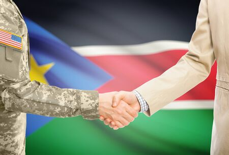 American soldier in uniform and civil man in suit shaking hands with adequate national flag on background - South Sudan
