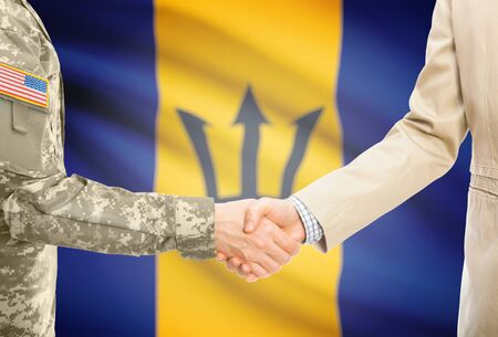 American soldier in uniform and civil man in suit shaking hands with adequate national flag on background - Barbados Stock Photo