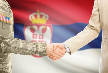 American soldier in uniform and civil man in suit shaking hands with adequate national flag on background - Serbia