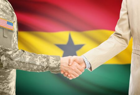 American soldier in uniform and civil man in suit shaking hands with adequate national flag on background - Ghana
