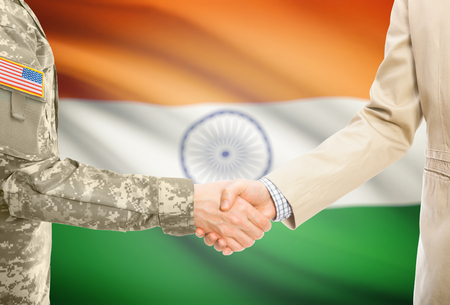 American soldier in uniform and civil man in suit shaking hands with adequate national flag on background - India
