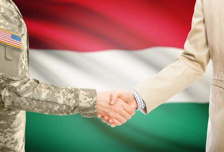 American soldier in uniform and civil man in suit shaking hands with adequate national flag on background - Hungary Stock Photo