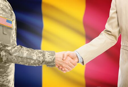 American soldier in uniform and civil man in suit shaking hands with adequate national flag on background - Chad