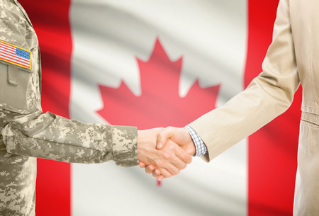 American soldier in uniform and civil man in suit shaking hands with adequate national flag on background - Canada Stock Photo