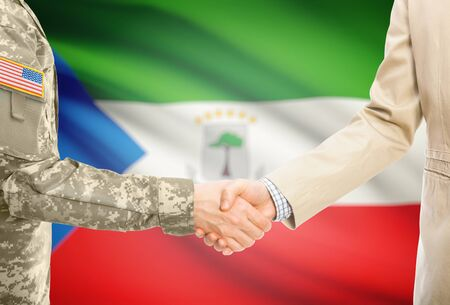 American soldier in uniform and civil man in suit shaking hands with adequate national flag on background - Equatorial Guinea