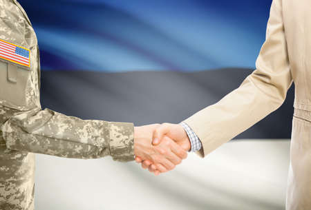 American soldier in uniform and civil man in suit shaking hands with adequate national flag on background - Estonia