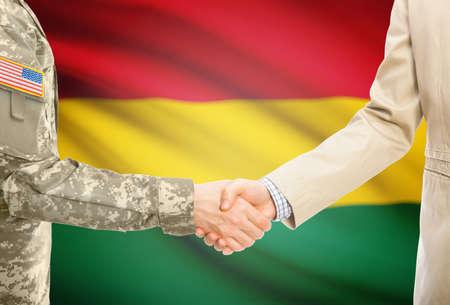 Soldado estadounidense en uniforme y hombre civil en traje de estrecharme la mano con una bandera nacional adecuada en el fondo - Bolivia