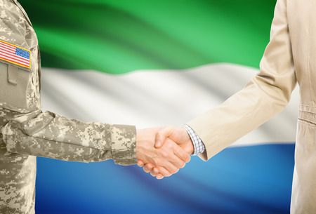 American soldier in uniform and civil man in suit shaking hands with adequate national flag on background - Sierra Leone