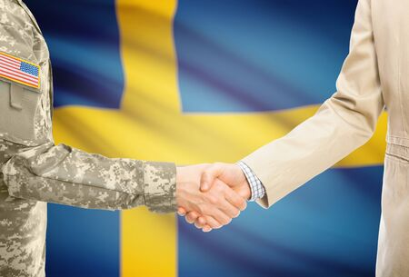 American soldier in uniform and civil man in suit shaking hands with adequate national flag on background - Sweden