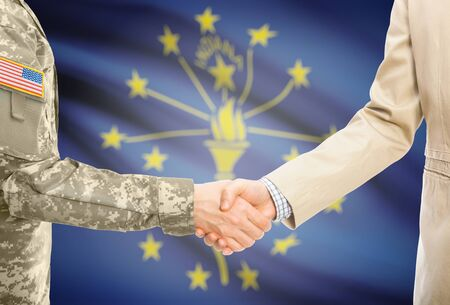 American soldier in uniform and civil man in suit shaking hands with certain USA state flag on background - Indiana