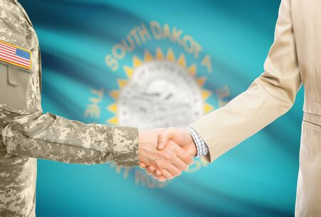 American soldier in uniform and civil man in suit shaking hands with certain USA state flag on background - South Dakota Stock Photo