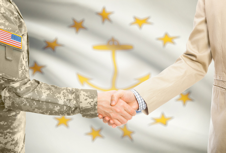American soldier in uniform and civil man in suit shaking hands with certain USA state flag on background - Rhode Island